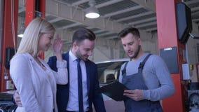 La familia en servicio del coche, los consumidores jovenes de los pares consulta con el técnico sobre mantenimiento auto y da las almacen de video
