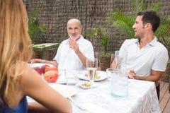 La familia escucha para engendrar mientras que habla en jardín Imagen de archivo libre de regalías