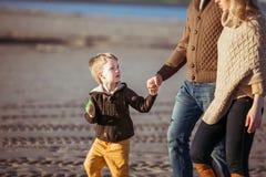 La familia está caminando a lo largo de la playa Foto de archivo