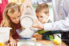 La familia está cociendo las galletas Foto de archivo libre de regalías