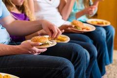 La familia está comiendo la hamburguesa o los alimentos de preparación rápida Imagen de archivo libre de regalías