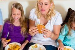 La familia está comiendo la hamburguesa o los alimentos de preparación rápida Foto de archivo libre de regalías