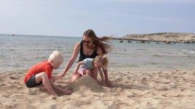 La familia está defendiendo el castillo de la arena en la playa el mar metrajes