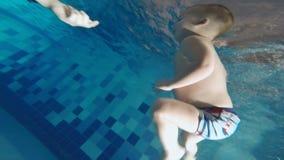 La familia está nadando en la piscina Un pequeño hijo hace un salto en el agua del puente de la piscina y con éxito metrajes