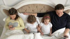 La familia está utilizando los dispositivos móviles que mienten en la cama durante fin de semana en casa Dos niños están sostenie almacen de metraje de vídeo
