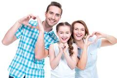 La familia europea feliz con el niño muestra la forma del corazón Foto de archivo libre de regalías