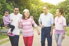 La familia extensa feliz camina junta en el parque imágenes de archivo libres de regalías