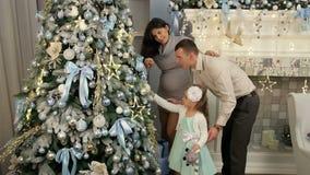 La familia feliz adorna el árbol de navidad Embarazada almacen de video