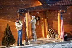 La familia feliz adorna la casa de madera para la Navidad Fotografía de archivo libre de regalías