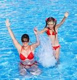 La familia feliz aprende nadada del niño en piscina. Imagen de archivo libre de regalías