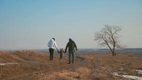 La familia feliz camina en prado de la primavera Paternidad, estación y concepto de la gente almacen de metraje de vídeo