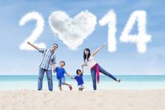 La familia feliz celebra el Año Nuevo 2014 en la playa Fotografía de archivo