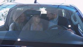 La familia feliz compra el nuevo coche, sonrisa femenina y masculino con la muchacha del niño examine el automóvil mientras que s almacen de metraje de vídeo