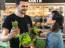 La familia feliz compra verduras Familia alegre de tres tomates que eligen en el departamento vegetal de supermercado o de mercad fotografía de archivo