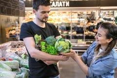 La familia feliz compra verduras Familia alegre de tres tomates que eligen en el departamento vegetal de supermercado o de mercad imagen de archivo libre de regalías