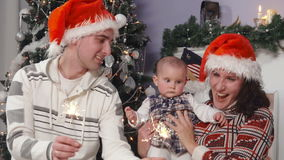 La familia feliz con el bebé en sombreros del ` s de Papá Noel disfruta de las luces de Bengala metrajes