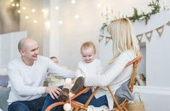 La familia feliz con el bebé pasa alegre tiempo de la casa Imágenes de archivo libres de regalías