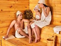 La familia feliz con el niño en sauna relajante del sombrero pasa fines de semana Fotografía de archivo
