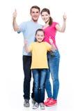La familia feliz con el niño muestra los pulgares encima de la muestra Imagen de archivo