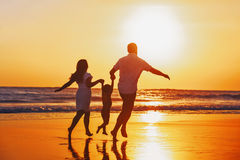 La familia feliz con el niño se divierte en la playa de la puesta del sol
