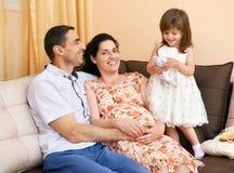 La familia feliz con el retrato interior de los niños, la mujer embarazada y el hombre, retrato hermoso de la gente se sienta en  Foto de archivo libre de regalías