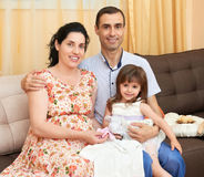 La familia feliz con el retrato interior de los niños, la mujer embarazada y el hombre, retrato hermoso de la gente se sienta en  Imagen de archivo libre de regalías