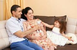 La familia feliz con el retrato interior de los niños, la mujer embarazada y el hombre, retrato hermoso de la gente se sienta en  Fotos de archivo