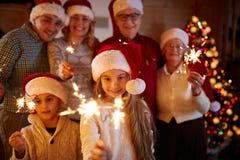 La familia feliz con las bengalas celebra la Navidad Fotos de archivo libres de regalías
