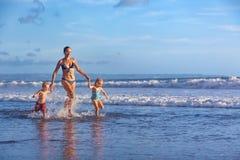 La familia feliz corre con la diversión a lo largo de la resaca de la playa de la puesta del sol Foto de archivo libre de regalías
