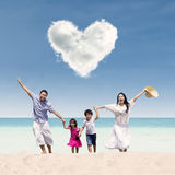 La familia feliz corre en la playa debajo de la nube del amor Imagen de archivo libre de regalías