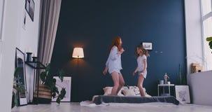 La familia feliz de hija linda y la madre joven que salta y que baila el rato de la cama se divierten durante días de fiesta en c almacen de video