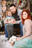 La familia feliz de la Navidad de personas del tres y de árbol de abeto con invierno del Año Nuevo de las cajas de regalo adornó  Imagen de archivo libre de regalías