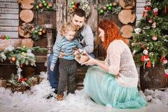La familia feliz de la Navidad de personas del tres y de árbol de abeto con invierno del Año Nuevo de las cajas de regalo adornó  Imágenes de archivo libres de regalías
