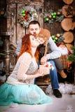 La familia feliz de la Navidad de personas del tres y de árbol de abeto con invierno del Año Nuevo de las cajas de regalo adornó  Foto de archivo