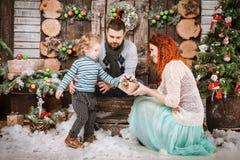 La familia feliz de la Navidad de personas del tres y de árbol de abeto con invierno del Año Nuevo de las cajas de regalo adornó  Foto de archivo libre de regalías