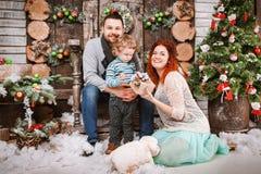 La familia feliz de la Navidad de personas del tres y de árbol de abeto con invierno del Año Nuevo de las cajas de regalo adornó  Fotografía de archivo libre de regalías