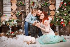 La familia feliz de la Navidad de personas del tres y de árbol de abeto con invierno del Año Nuevo de las cajas de regalo adornó  Imagen de archivo