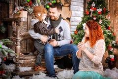 La familia feliz de la Navidad de personas del tres y de árbol de abeto con invierno del Año Nuevo de las cajas de regalo adornó  Fotografía de archivo