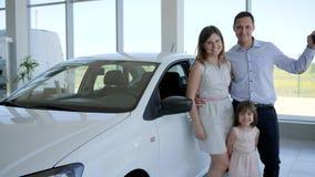 La familia feliz del retrato que compra el nuevo auto, coche familiar, llaves del automóvil en la mano del ` s del cliente, gente almacen de video