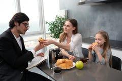 La familia feliz desayuna en casa imagen de archivo