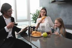 La familia feliz desayuna en casa foto de archivo