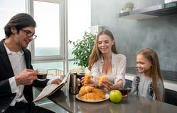 La familia feliz desayuna en casa fotografía de archivo libre de regalías