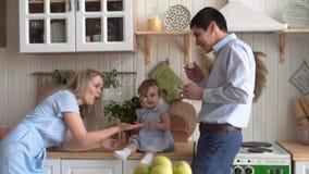 La familia feliz en la cocina, en donde la hija se sienta en la tabla, pap? infla las burbujas de jab?n, mam? coge sus manos metrajes
