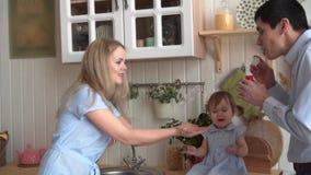 La familia feliz en la cocina, en donde la hija se sienta en la tabla, pap? infla las burbujas de jab?n, mam? coge sus manos almacen de metraje de vídeo