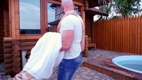 La familia feliz en el umbral de la casa, el marido da vuelta a su esposa a una nueva cabaña, diversión parents en el césped dela almacen de metraje de vídeo