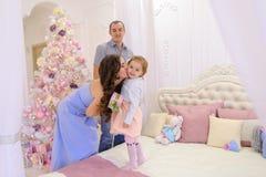 La familia feliz en el umbral de la Navidad comunica con cada uno más allá del horizonte Imagen de archivo libre de regalías