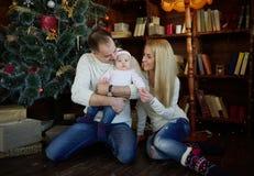 La familia feliz en la Navidad adornó el sitio Imagenes de archivo