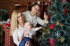 La familia feliz en la Navidad adornó el sitio Foto de archivo libre de regalías