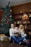 La familia feliz en la Navidad adornó el sitio Foto de archivo