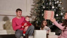 La familia feliz enojoying regalos de Navidad metrajes